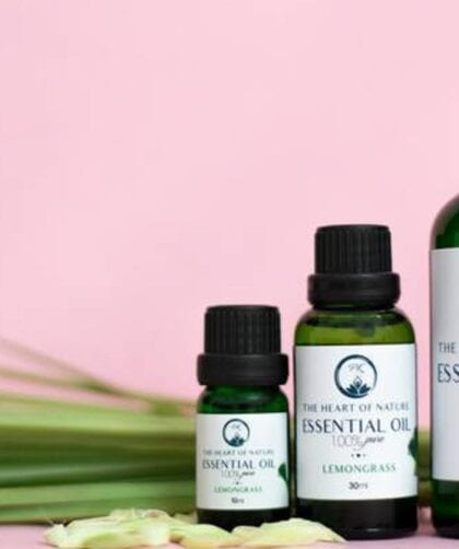 3 bottles of essential oil of different sizes with pink background
