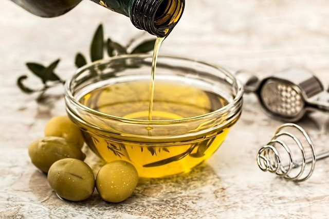 bottle pouring olive oil into small bowl
