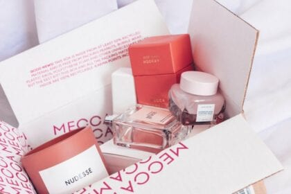 Gift box with several salmon-coloured cosmetics displaying