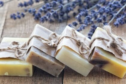 four natural handmade soaps over wooden table with lavender flowers