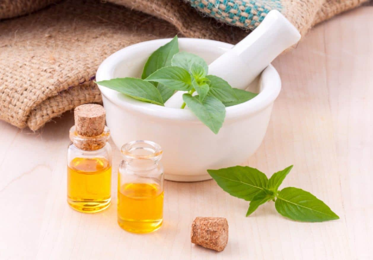 herbs in mortar and two small bottles of oil