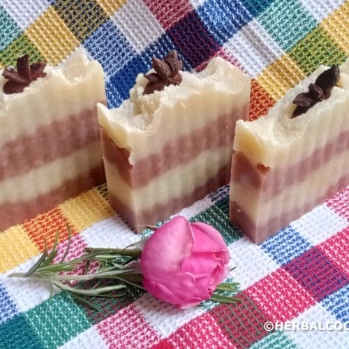3 pretty soap bars with layered red and cream colors with star anis on top and decorated with a rose
